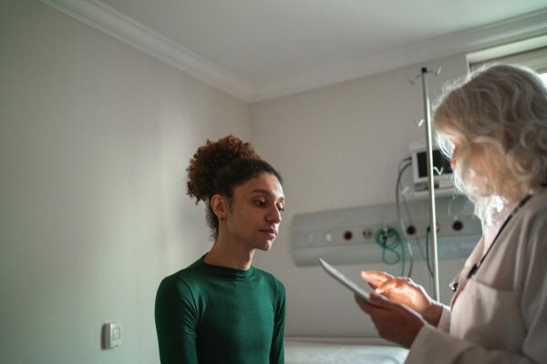 A person speaks with a doctor inside an examination room.