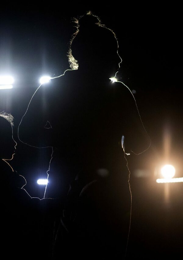 Two silhouettes, one of a woman and one of a girl are illuminated by car headlights.