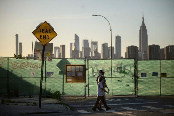 Pedestrians pass a 'dead end' sign before the Manhattan city skyline.