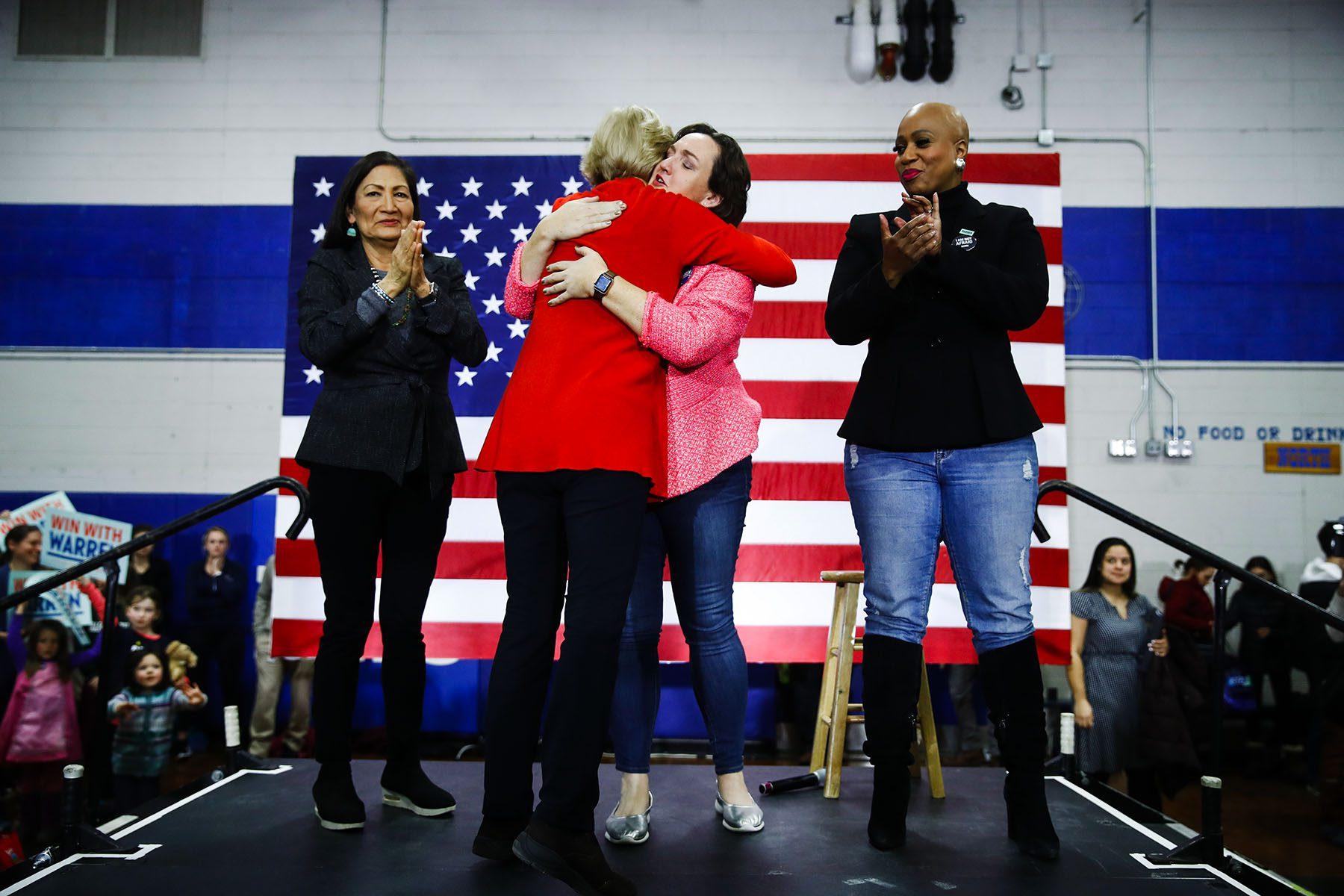 Warren hugs Katie Porter while Deb Haaland and Ayanna Pressley