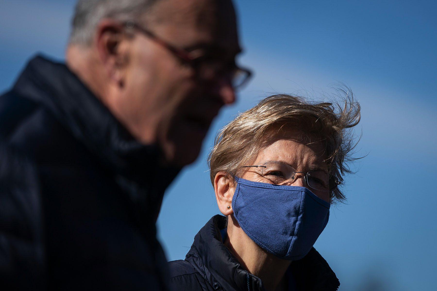 Elizabeth Warren wears a blue face masks and looks on while Chuck Schumer speaks.