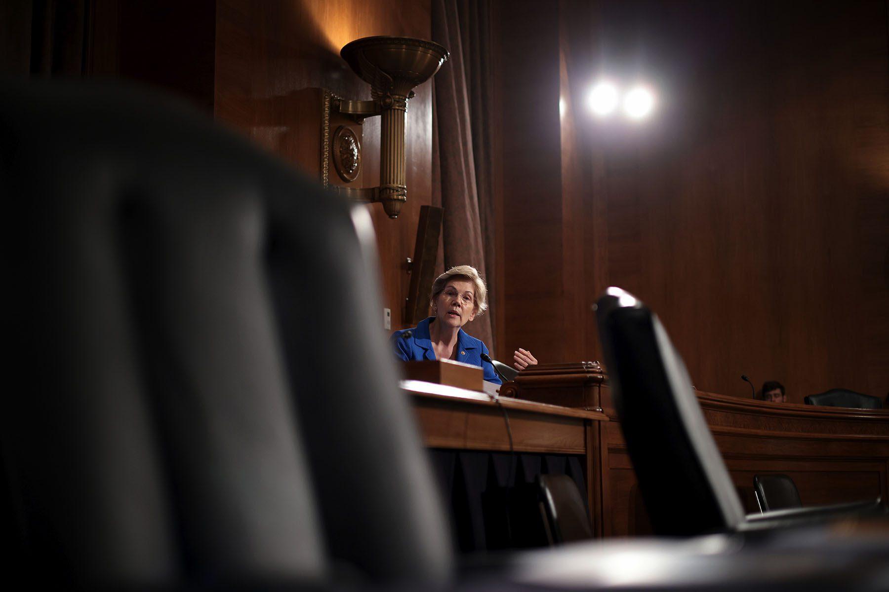 Elizabeth Warren sits behind a desk.