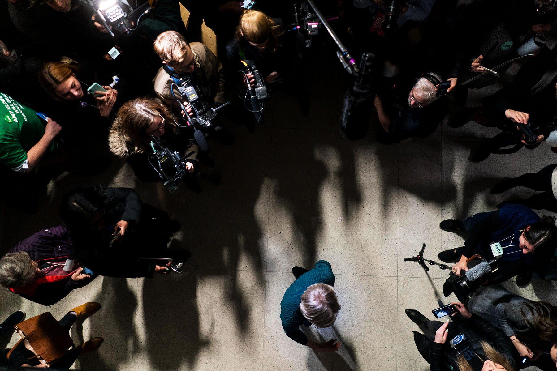 A bird's eye view of Elizabeth Warren surrounded by press.
