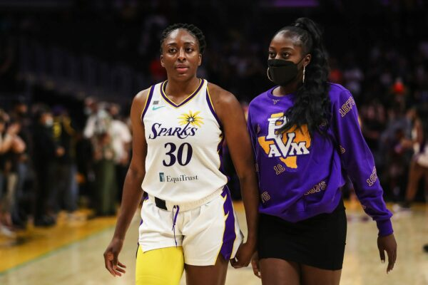 Nneka Ogwumike and Chiney Ogwumike walk together in a basketball stadium.