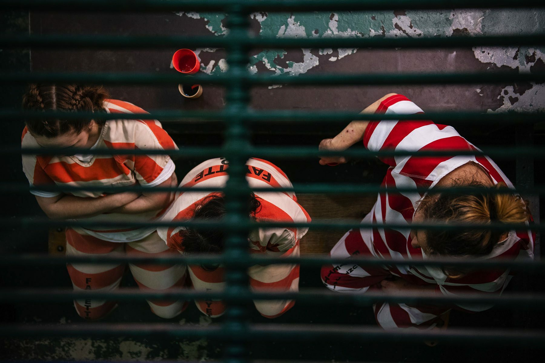 Three female inmates wearing orange and white striped prison uniforms sit on a bench.